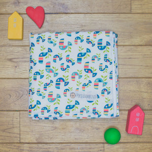 An organic Poco Bambino blanket. The print is a toucan design.