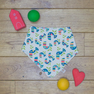 An organic Poco Bambino dribble bib. The print is a multicoloured toucan design.