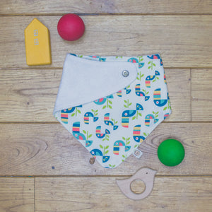 An organic Poco Bambino dribble bib. The print is a multicoloured toucan design. One corner is folded up to show the organic cotton and bamboo terry reverse