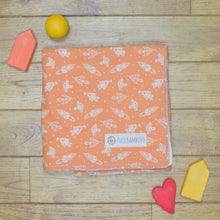 Load image into Gallery viewer, An organic Poco Bambino blanket. The print is orange with white rockets