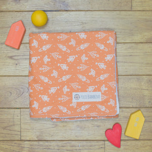 An organic Poco Bambino blanket. The print is orange with white rockets