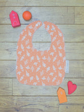 Load image into Gallery viewer, An organic Poco Bambino bib. The print is orange with a white rockets design.