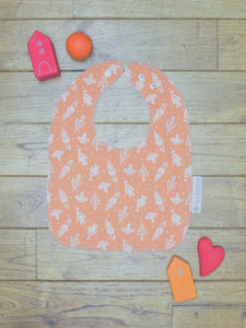 An organic Poco Bambino bib. The print is orange with a white rockets design.