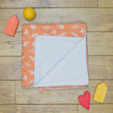 Load image into Gallery viewer, An organic Poco Bambino blanket. The print is orange with white rockets. One corner is folded up to show the organic cotton and bamboo fleece reverse