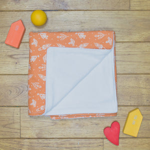 An organic Poco Bambino blanket. The print is orange with white rockets. One corner is folded up to show the organic cotton and bamboo fleece reverse
