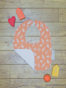An organic Poco Bambino bib. The print is orange with a white rockets design. One corner is folded up to show the organic cotton and bamboo terry reverse