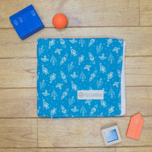 Load image into Gallery viewer, An organic Poco Bambino blanket. The print is dark blue with white rockets
