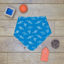 Load image into Gallery viewer, An organic Poco Bambino dribble bib. The print is blue with white space rockets.