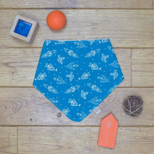 An organic Poco Bambino dribble bib. The print is blue with white space rockets.