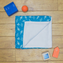 Load image into Gallery viewer, An organic Poco Bambino blanket. The print is dark blue with white rockets. One corner is folded up to show the organic cotton and bamboo fleece reverse