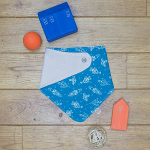 An organic Poco Bambino dribble bib. The print is blue with white space rockets. One corner is folded up to show the organic cotton and bamboo terry reverse