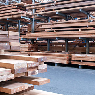 Wooden studs and plywood stacked inside a warehouse.