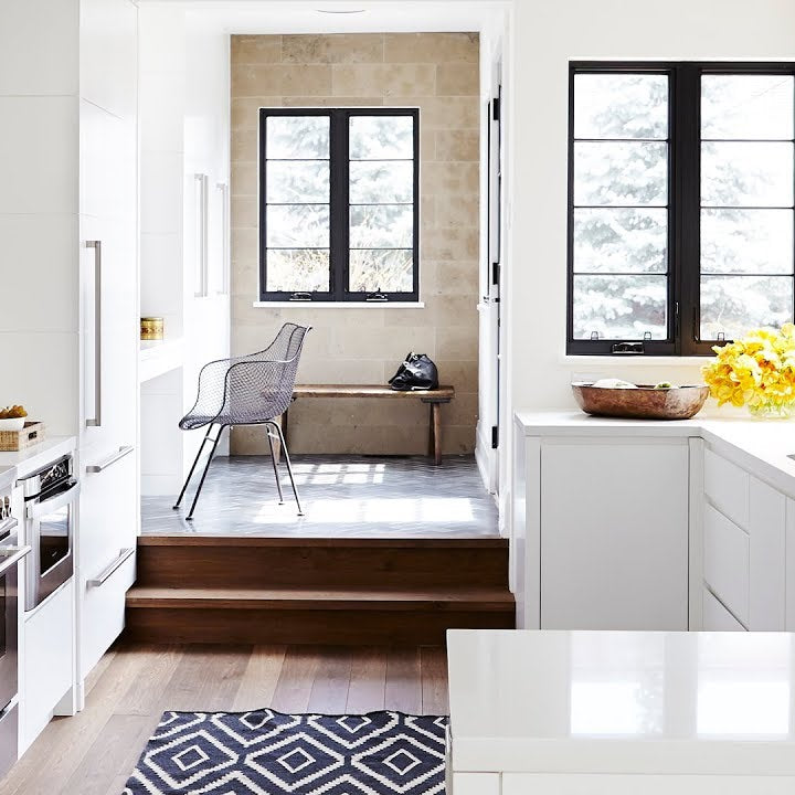 A renovated kitchen with white countertop and cabinets.