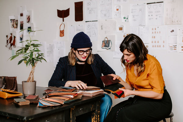 two women look at leather swatches at a table