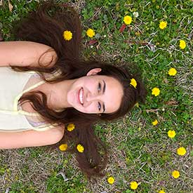 Dandelions shaped like a heart around girl's head while lying in the grass.  Taken from above angle.  Tublr style photo for spring