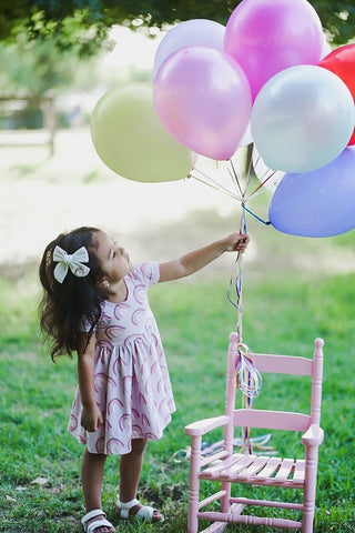 toddler in rainbow dress with balloons tied to little pink chair
