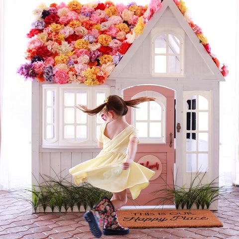 girl twirling in yellow dress in front of playhouse covered in pastel faux flowers