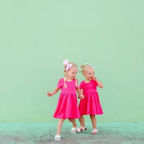 twins in matching pink twirl dresses standing in front of mint colored wall