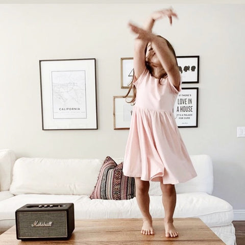little girl dancing in pink twirl dress on coffee table