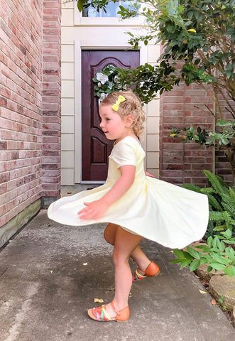 toddler in yellow twirl dress spinning around in front of her front door
