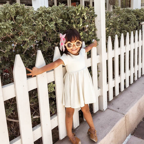 cute kid in yellow dress leaning on white picket fence wearing flower shaped sunglasses