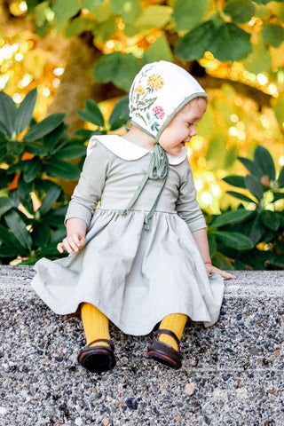 toddler in green twirl dress, yellow tights and embroidered bonnet sitting on bench