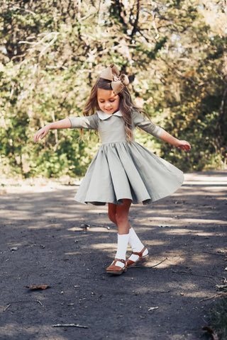 5 year old girl twirling in a park wearing green holiday dress and bow