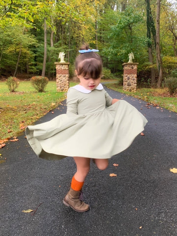 toddler twirling in green dress, orange socks and boots with bow in hair