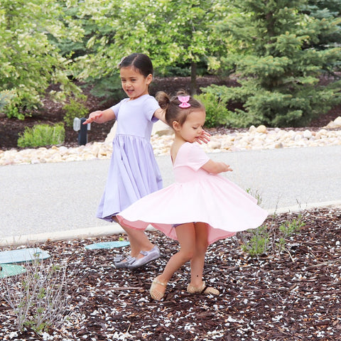 little girl twirling in pink dress and little girl in lavender twirl dress
