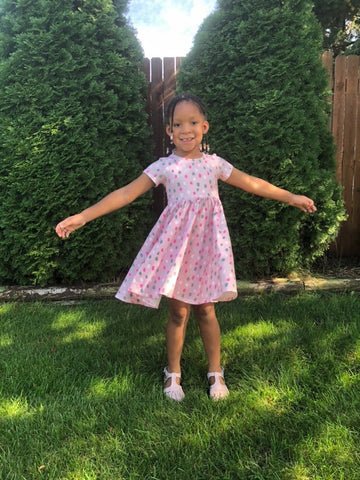 dot print twirl dress from ollie jay on young girl standing on grass