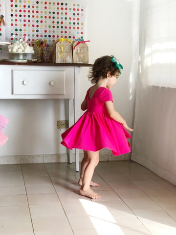young girl in bright pink twirling dress