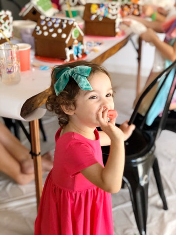 little girl eating candy at birthday party