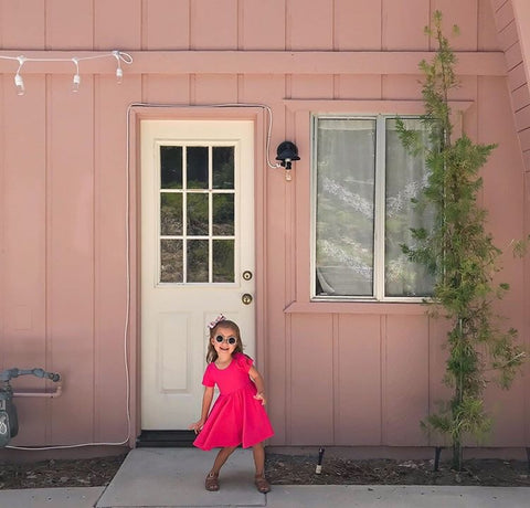little girl in pink dress playing in front of a pink cabin