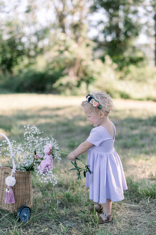 toddler in a field playing with a basket of flowers in a purple dress