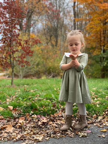 3 year old standing in field of leaves looking into her hand