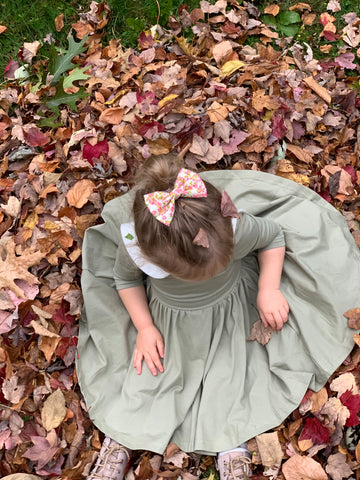 toddler sitting in a bed of fallen leaves in a cute twirl dress