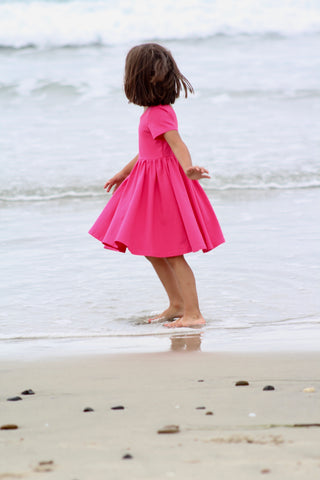 young girl in pink twirl dress playing on the beach shoreline
