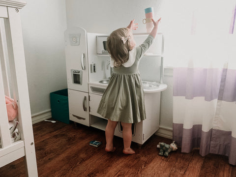 2 year old playing kitchen in her bedroom with a pretty green dress