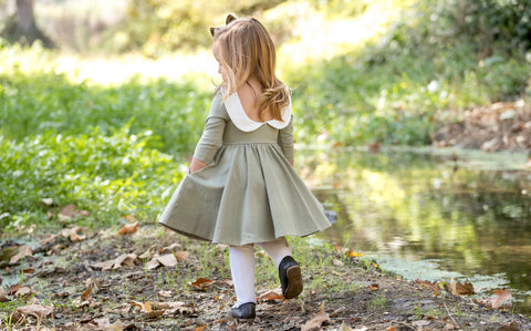 toddler walking near a creek with hands in pockets of her green fall dress
