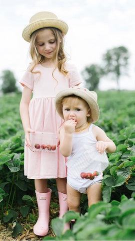 young girl in pink dress and baby at strawberry field