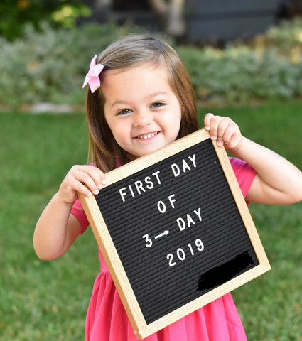 three year old girl holding first day of school sign in pink dress and pink bow