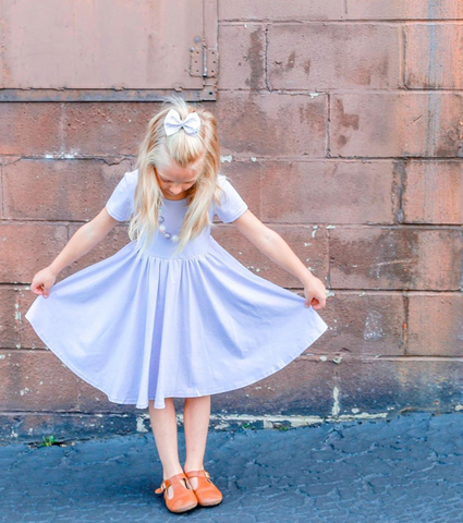 little girl in front of brick wall wearing lavender twirl dress
