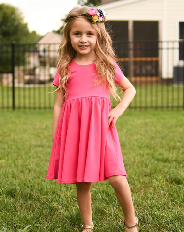 toddler in pink dress posing for the camera hearing felt flower headband
