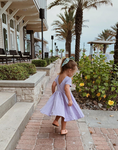 toddler girl walking down a sidewalk by the beach in a lavender twirling dress