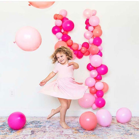 curly haired girl dancing in twirl dress in front of balloon collage that shows number four