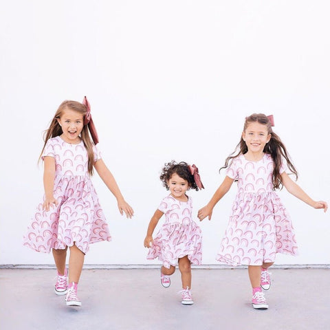 three girls running and playing in front of a white wall wearing rainbow dresses