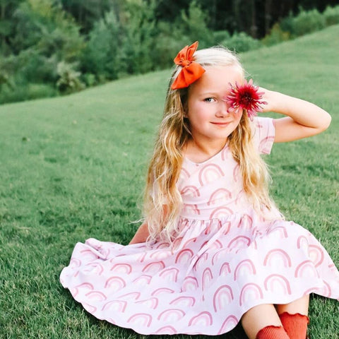 girl sitting in grass with flower over eye in rainbow dress