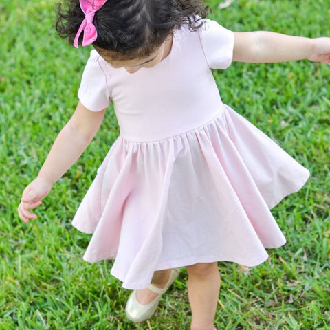 girl standing on grass in pink twirling dress