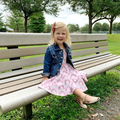 toddler girl sitting on park bench with jean jacket and rainbow dress