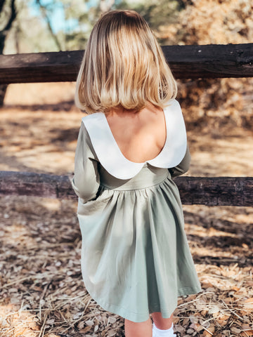 young girl standing near fence modeling back of her new dress